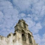 Bell tower of Mission San Juan church with clouds behind it.