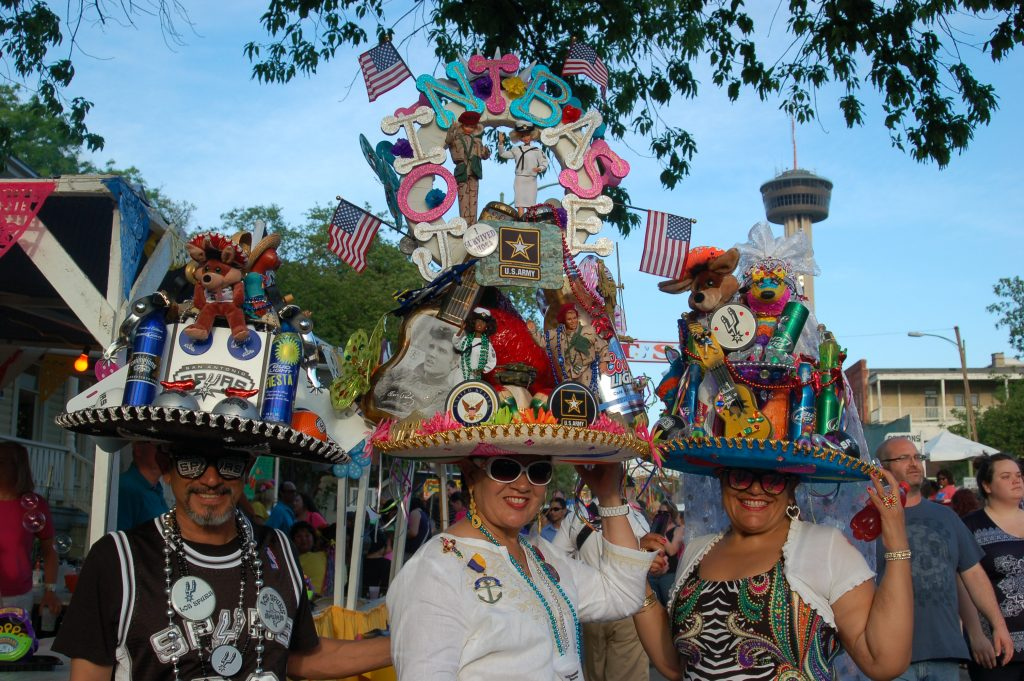Three friends show off their sombreros piled high with decorations and San Antonio memorabilia.