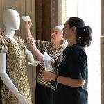 Curators Michael and Victoria Haynes clean a mannequin in preparation to display Queen Lita's Fiesta coronation gown in Johanna Steves' bedroom.