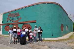 """Community supporters hold signs reading, """"Esta lugar es importante - This place matters,"""" in front of Lerma's Nite Club."""