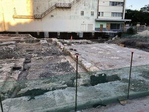 Photo of the uncovered foundation of St. James African Methodist Episcopal church with the Alameda Theater in the background. The cornerstone is wrapped in a black covering.