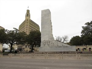 West side of the Alamo Cenotaph with the walls of the Long Barrack and the Emily Morgan Hotel in the background.